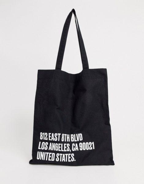 ASOS DESIGN - Schwarze Tragetasche aus Bio-Baumwolle mit weißem Textprint